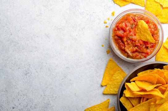 Traditional mexican homemade salsa sauce in a glass bowl and a b
