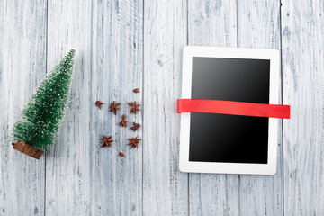 Christmas design red flowers carnation, spruce and tablet with red ribbon on old grey wooden background