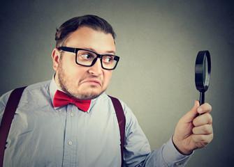 Curious man using magnifier