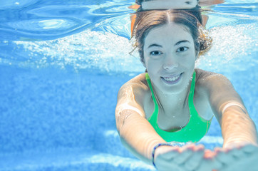 Girl swims in swimming pool underwater, happy active teenager dives and has fun under water, kid fitness and sport on family vacation