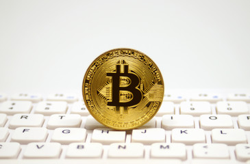 Golden symbolic coin of bitcoin on white keyboard