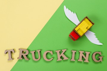 Abstract picture of a truck with wings and a word of trucking. Green background. Cargo transportation of the future