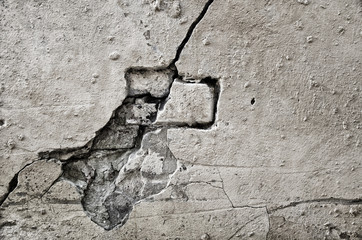 Peeling plaster with an old brick wall seen through the hole (as an abstract grungy background like...