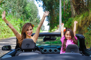 Close up of beautiful woman wearing a black dress and a red flower in her head and her gorgeous daugher a pink dress with a red flower in her head and posing inside of a luxury black car on a road