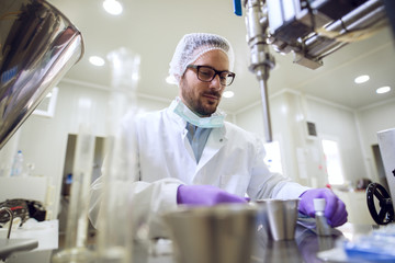 Close up of serious focused professional scientist bearded young man sitting and working at laboratory machine with metal flasks and bottles in front.