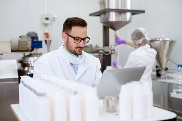 Close up of cheerful focused professional happy entrepreneur man sitting with a laptop on the desk with a row of white cream bottles while assistant standing behind and working on a fabric machine.
