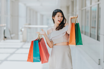 Happy Asian beautiful woman looking and smiling at shopping bag in her both hand indoor.