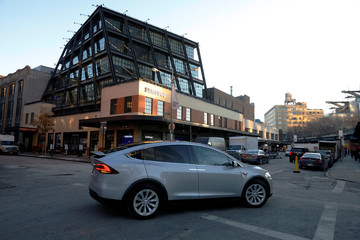 A Tesla drives past Tesla Motors' new showroom at Manhattan's Meatpacking District in New York City