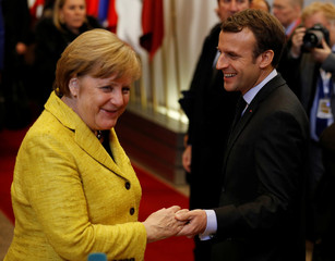 German chancellor Angela Merkel says farewell to French President Emmanuel Macron at the end of the first day of the European Union leaders summit in Brussels, Belgium