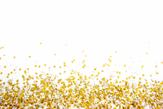 Golden shiny confetti on a white background.
