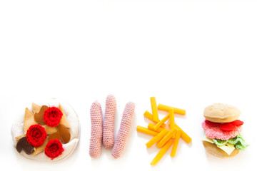 The toy food is sewn from fabric and knitted from yarn. Children's game in a shop or cafe.