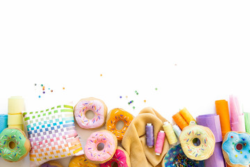 A woman sews from a cloth donuts for a children's game. Not real food made of cloth and thread. Crocheted from yarn.