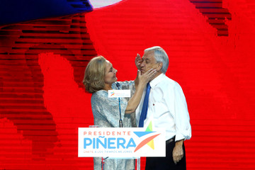 Cecilia, Wife of Chilean presidential candidate Sebastian Pinera, cleans his face during their campaign closing rally in Santiago,