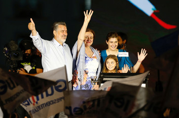 Chilean presidential candidate Alejandro Guillier stands next to his wife Cristina Farga while waving to supporters during his campaign closing rally in Santiago, Chile