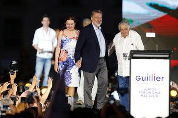 Chilean presidential candidate Alejandro Guillier, his wife Cristina Farga, and former Uruguayan president Jose Mujica attend a campaign closing rally in Santiago, Chile