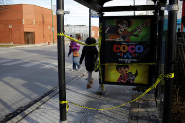 Two women walk past a transit bus shelter, where a 18-year-old man was killed and a 17-year-old man was wounded, in Chicago