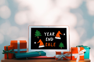 Christmas, new year, presents box and laptop computer with year end sale advertisement on wooden table over bokeh wall background and copy text space for writing messages