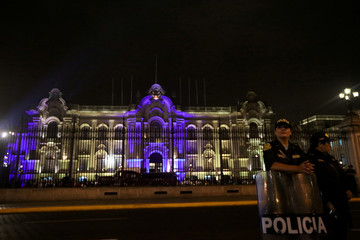 Police officers stand outside of the Government Palace in Lima