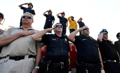 Emergency personnel salute as a procession of firefighting vehicles passes through Santa Paula, while carrying the body of a fellow firefighter who was killed today battling the Thomas wildfire near Fillmore, California