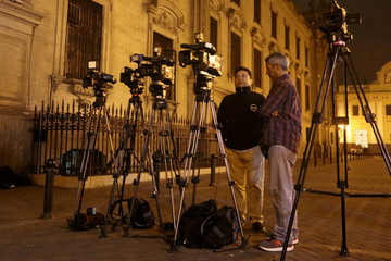Journalists stand outside the Government Palace in Lima, Peru