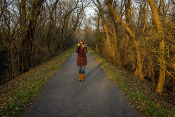 woman standing on forest trail taking photo
