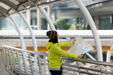 Happy female tourist with suitcase exploring map while standing in city building