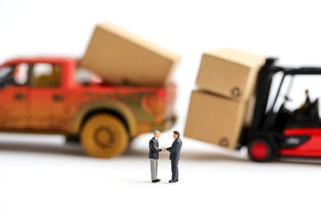 Miniature people : businessmen hand checking, standing in front of Pickup truck