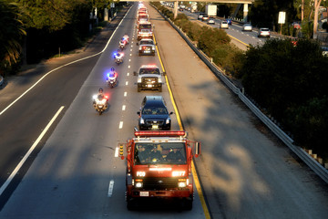 A procession of firefighting vehicles passes through Santa Paula while carrying the body of a fellow firefighter who was killed today battling the Thomas wildfire