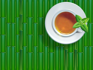 Black tea cup with mint leaves on bamboo background.