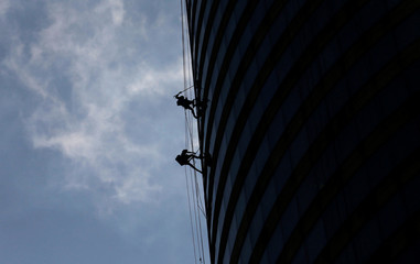 Workers clean glass panels at the west tower of the World Trade Center in Colombo