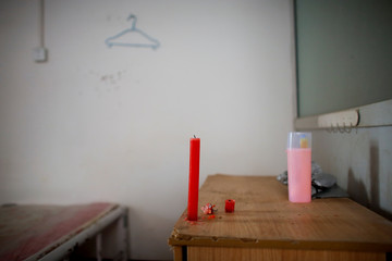 A candle stands on a table in a room that used to be inhabited by migrant workers in a low-cost dormitory that has been cut off from water and electricity supply in Beijing