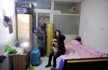 Ms Xiang, a migrant worker from Hebei province and her partner pose with their dog in their room that has been cut off from water and electricity supply in Beijing