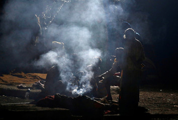 People warm themselves around a fire along a roadside on a cold winter morning in Mumbai