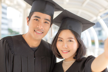 Young Asian People Students wearing Graduation hat and gown, city background, People with Graduation Concept. Woman Holding Smartphone for Selfie.