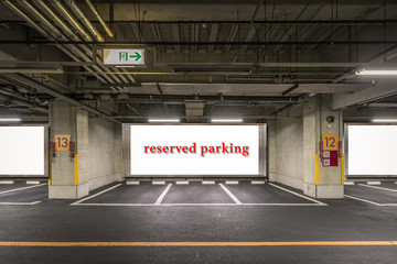 Parking garage underground interior with reserved parking apaces sign board