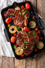 Spicy hot T Bone Steak with tomato, chili and onion in a grill pan. Vertical top view