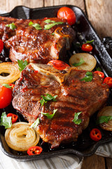 Fried T-Bone steak with tomatoes, chili and onions in a grill pan close-up. vertical