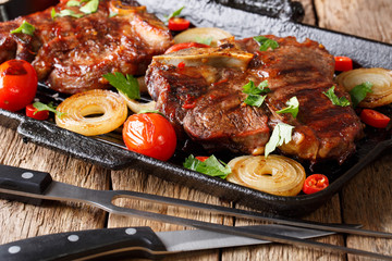 T-Bone steak with tomatoes and onions in a grill frying pan close-up. horizontal