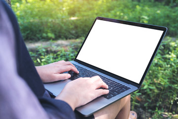 Mockup image of business woman using and typing on laptop with blank white screen , sitting at outdoor with nature background