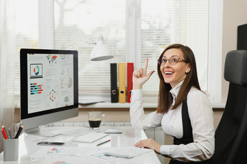 Beautiful business woman in suit and glasses working at computer with documents in light office, looking up