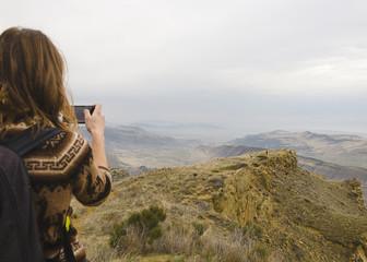 ragazza in montagna fa la foto con telefonino