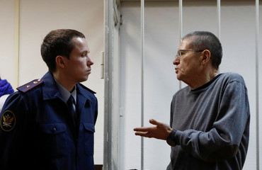 Russian former Economy Minister Alexei Ulyukayev, who was charged with accepting a bribe, talks to an official from the Russian prison service while he waits for the start of a court hearing in Moscow