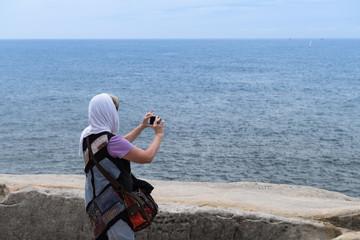 Frau mit Kopftuch fotografiert den Meerblick von der Küste mit dem Handy