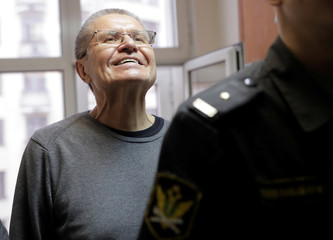 Russian former Economy Minister Alexei Ulyukayev, who was charged with accepting a bribe, smiles as he walks to the courtroom before the start of a court hearing in the court building in Moscow
