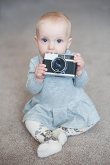 Cute baby girl playing with vintage camera. Close up portrait of little girl in grey dress