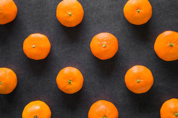 Fruit pattern of beautiful, fresh, orange mandarins on the dark background. Healthy sweet food concept. Mock up for fruits offers as advertising or web background, or other ideas.