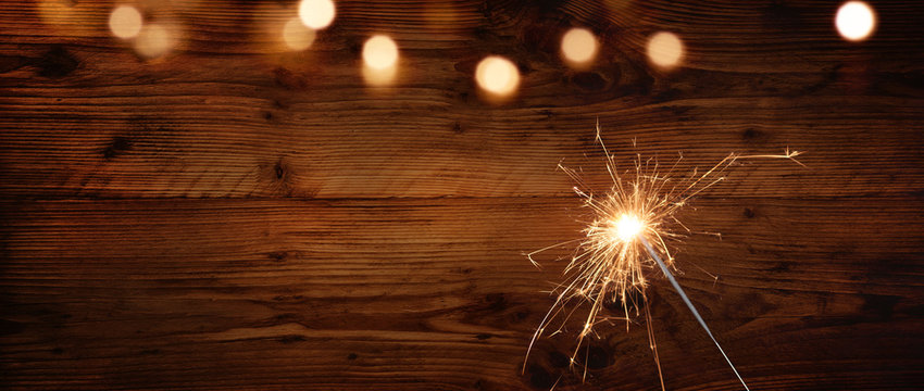 Rustic wooden wall with sparkler and bokeh