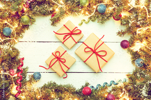 christmas wooden background with decor frame and three gift boxe