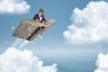 Mann fliegt auf einem Buch über die Wolken