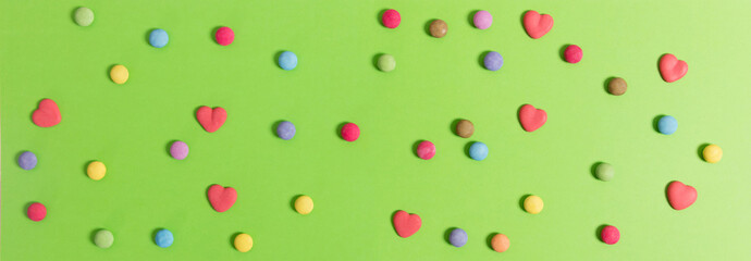 Colorful candies on green background, top view